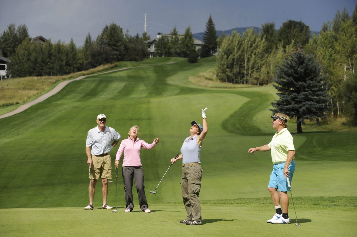Golfers, from left, Steve Speer, Kari Nelson, Heidi Theis and Paul Luebbers react after Theis missed a putt during The Moose's Loose scramble golf tournament Wednesday at Rollingstone Ranch Golf Club.