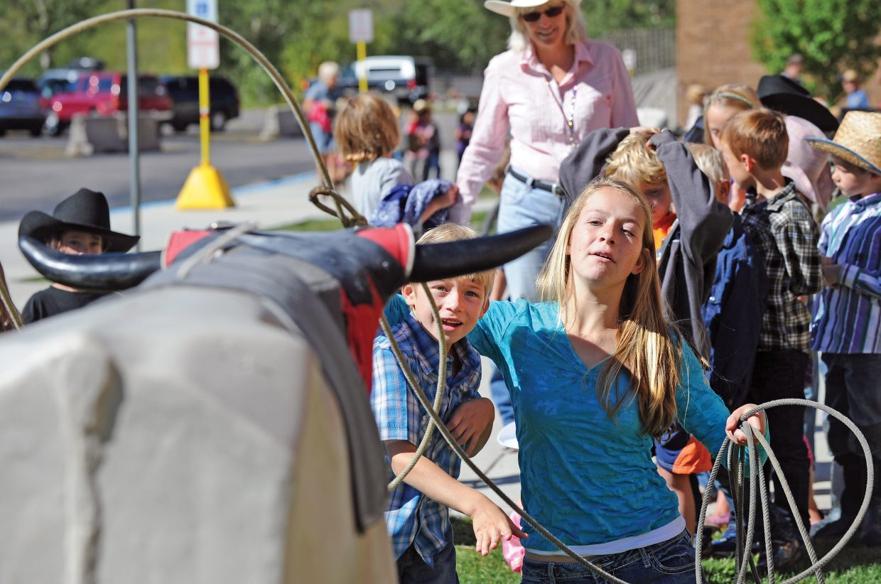Strawberry Park Elementary School kindergartner Luka Russell gets a helping hand from high school student Zava Zupan while learning to rope during Western Heritage Day at the school. The event was a chance for students to learn about Steamboat Springs history.