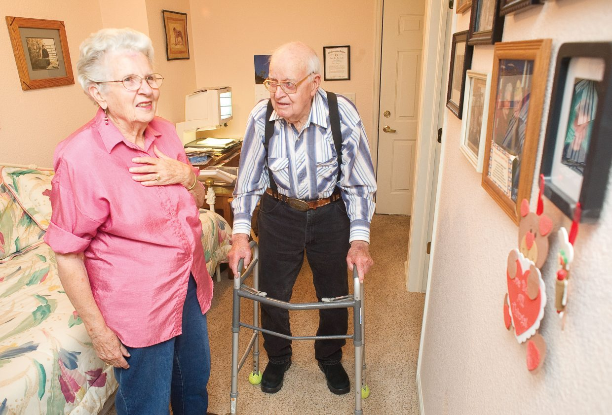 Betty and Lewis Kemry look at family portraits on the wall of their Steamboat Springs home.