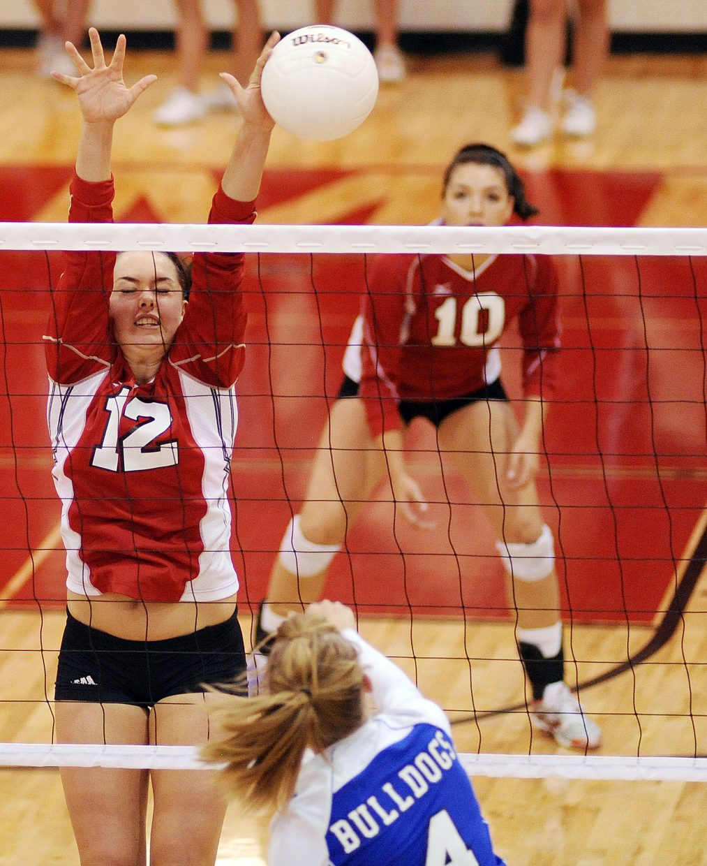 Steamboat's Amy Brodie closes her eyes but catches a piece of the ball on a block Thursday against Moffat County. The Sailors swept the Bulldogs, winning in three games.