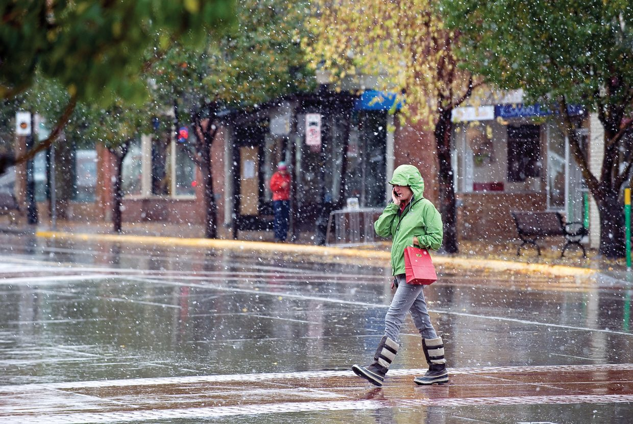 Meagan Bridges makes her way across Lincoln Avenue and through the snow in downtown Steamboat Springs on Thursday afternoon. A winter storm, which is expected to bring snow to the area, didn't disappoint as the first flakes of the season can be seen falling in the air.