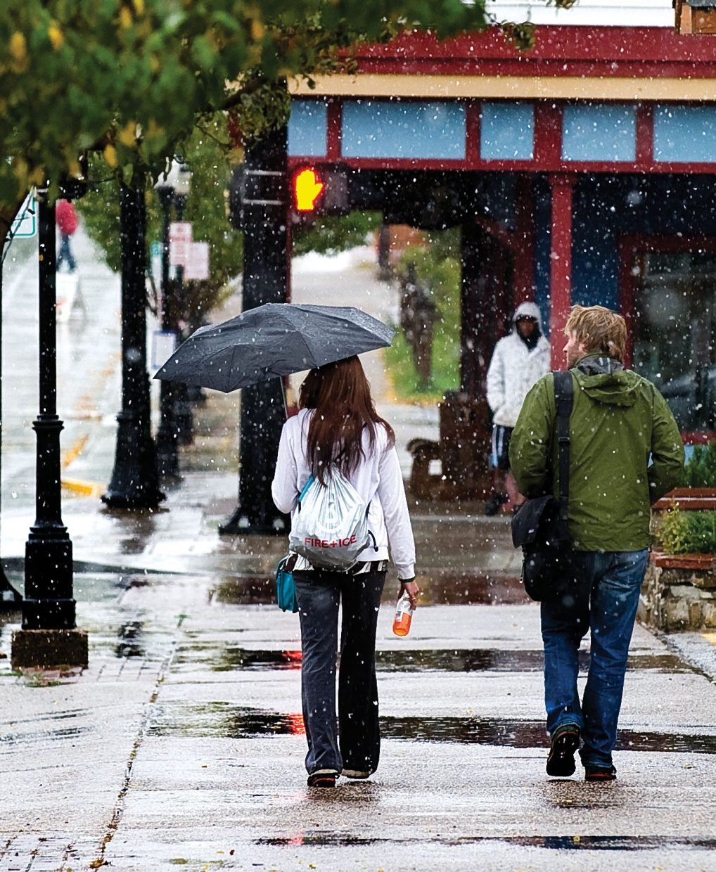 Abada O'Connell, left, and Graham Clark stroll through the falling snow Thursday afternoon on Lincoln Avenue.