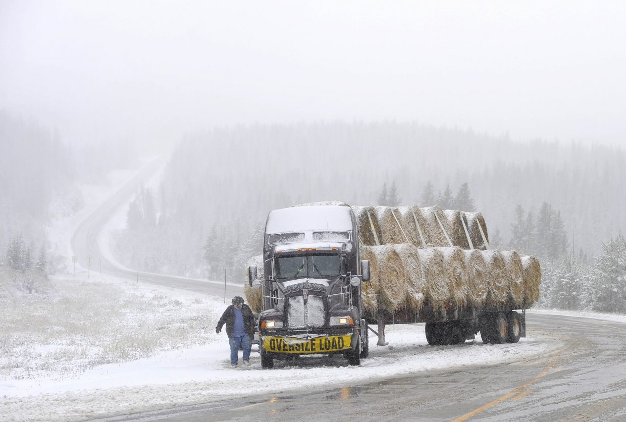 Trucker George Settelmeyer puts chains on his tires on U.S. Highway 40 after jackknifing during a snowstorm Thursday on Rabbit Ears Pass.