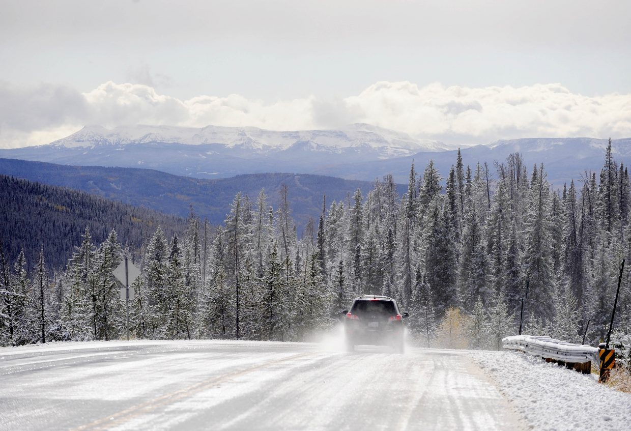 A car drives over the West Summit of Rabbit Ears Pass, which revealed fresh snow at the Flat Tops Wilderness Area on the horizon.