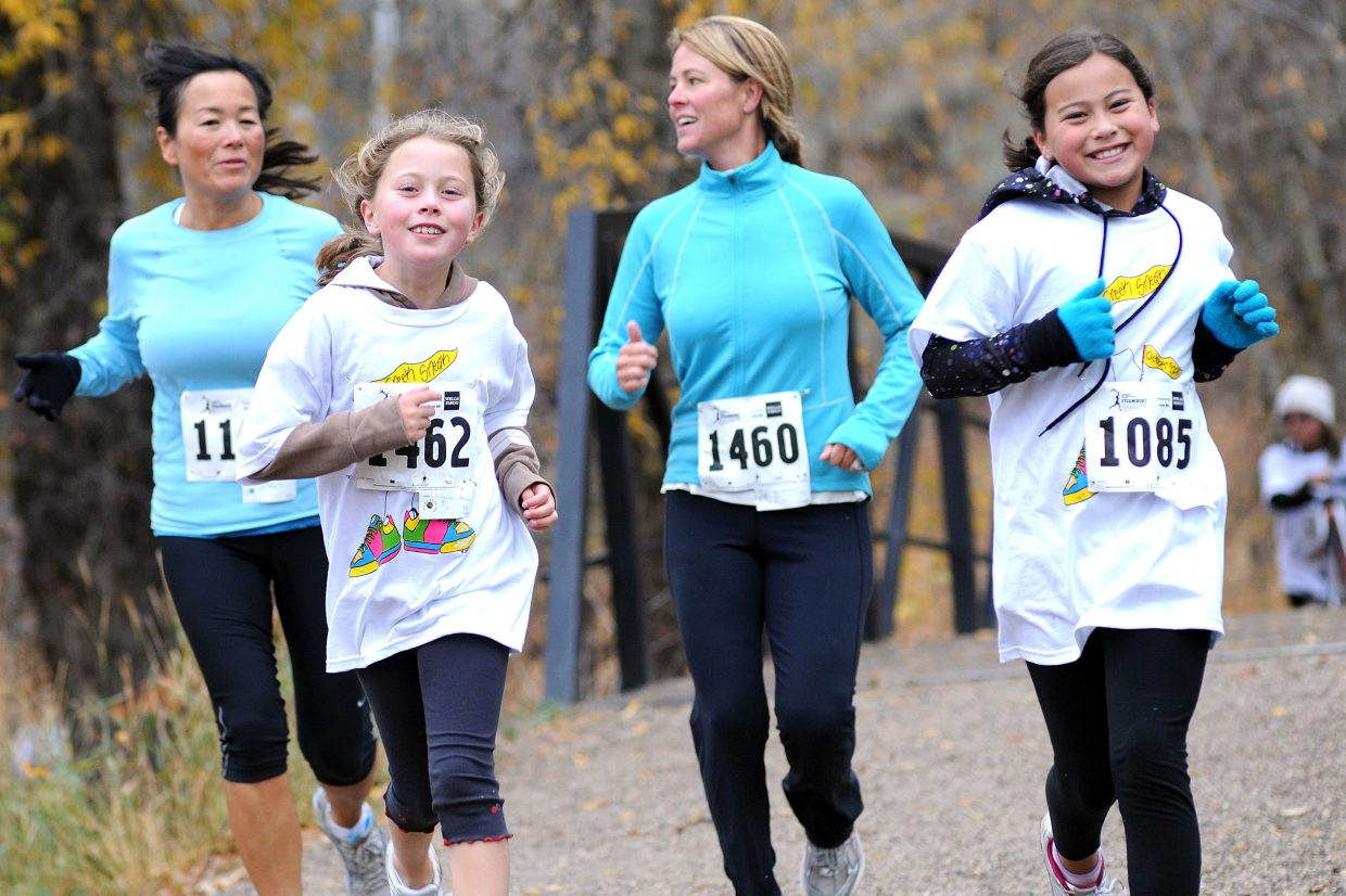 Alicia Mitchell, front left, and Mi-ri Frasier, front right, lead the way for Mischael Frasier, left, and Lori Mitchell during Saturday's Soda Creek Sneak 5-kilometer run. The run attracted more than 200 runners.