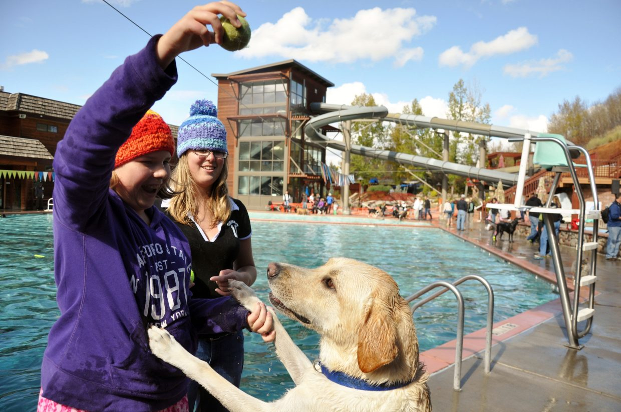 From left, Alexa and Erika Kipfer tease their dog Rowdy with a tennis ball Sunday at the Old Town Hot Springs during the pool's Poochy Paddle event.