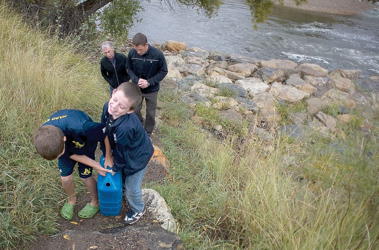 Steamboat Springs Middle School students Fischer Matthews, left, and Sam Fitzhugh carry a 5-gallon water container filled from the banks of the Yampa River back to the Deport Art Center. The demonstration was designed to give students a feel for what children in Uganda, who sometimes have to carry the containers a mile or more, go through every day to bring water to their families.