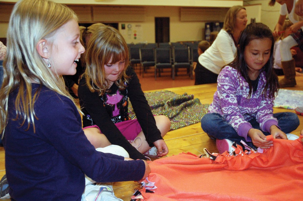 Bethany Leader, 8, left, chats with her friends, Kyra Wilson, 5, and Lily Archuleta, 8, as she ties knots in a fleece blanket Friday at Christian Heritage School. Students worked on the blankets that teacher Tracie Patterson will take to an orphanage in China next month.