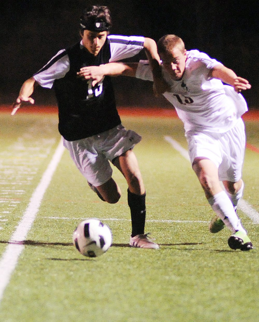 Steamboat's Alex Alfone wrestles with a Colorado Academy player on a run to the ball Saturday night.