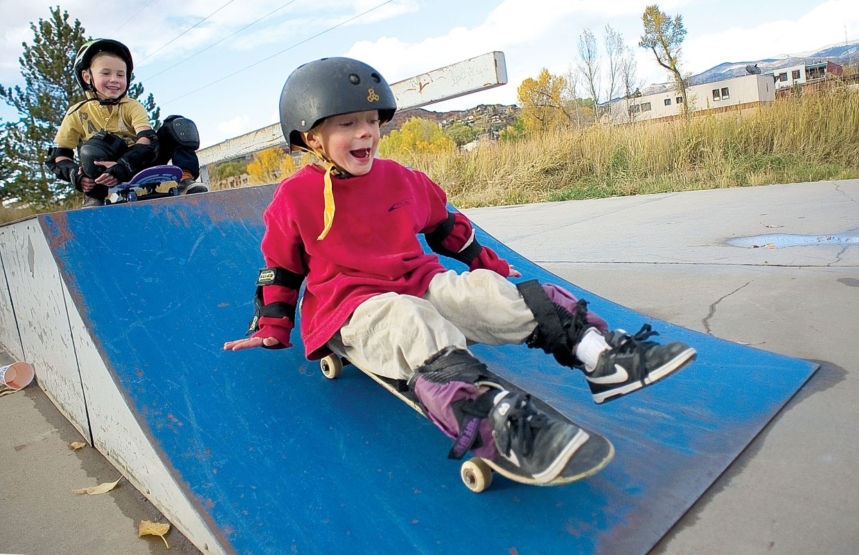 Wyatt Graves rides his skateboard down a ramp at the Howelsen Hill Skateboard Park on Monday afternoon while his skating buddy, Rowan Turek, waits for his turn. The two 5-year-olds took advantage of a slight break in Monday's cool, wet weather.
