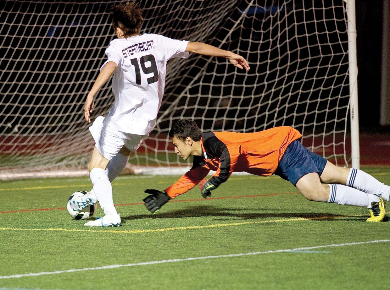 Steamboat Springs Mac Noel shoots the ball into the net past a diving Eagle Valley's Brandon Cano at the end of the first half of Tuesday night's game at Gardner Field in Steamboat Springs. The goal gave the Sailors a 3-0 lead in the game. The Sailors won, 7-1.