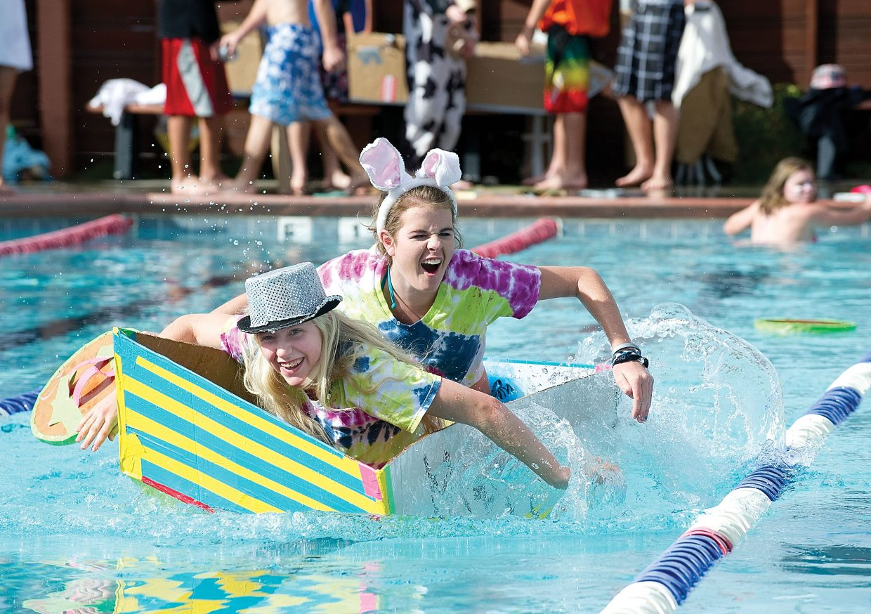 Steamboat Springs High School students Malia Fraioli, front, and Meg O'Connell make their way across the Old Town Hot Springs lap pool Friday morning as part of the annual Cardboard Classic Boat Race. The students designed the watercraft in Eric Nilsson's physics class and raced them as part of an exam. Students from Hayden High School also participated in the race, which was won by the Steamboat team of Sam Ogden, Jason Tweedy and Mathew Procyzyn.