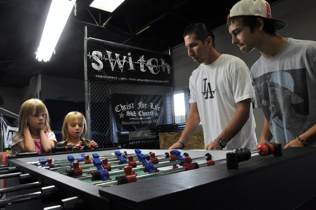 From left, Chloe and Courtney Chavarria watch Sk8 Church founder Buck Chavarria and CJ Appel play a game of foosball Thursday at the church.