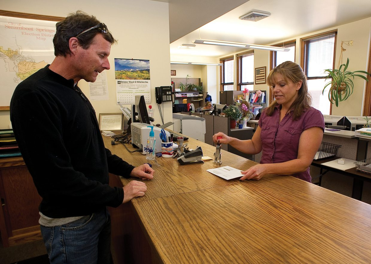 Resident Jim Ruggiero drops off his ballot to Routt County Clerk Barbara Houston on Wednesday morning at the Routt County Courthouse.