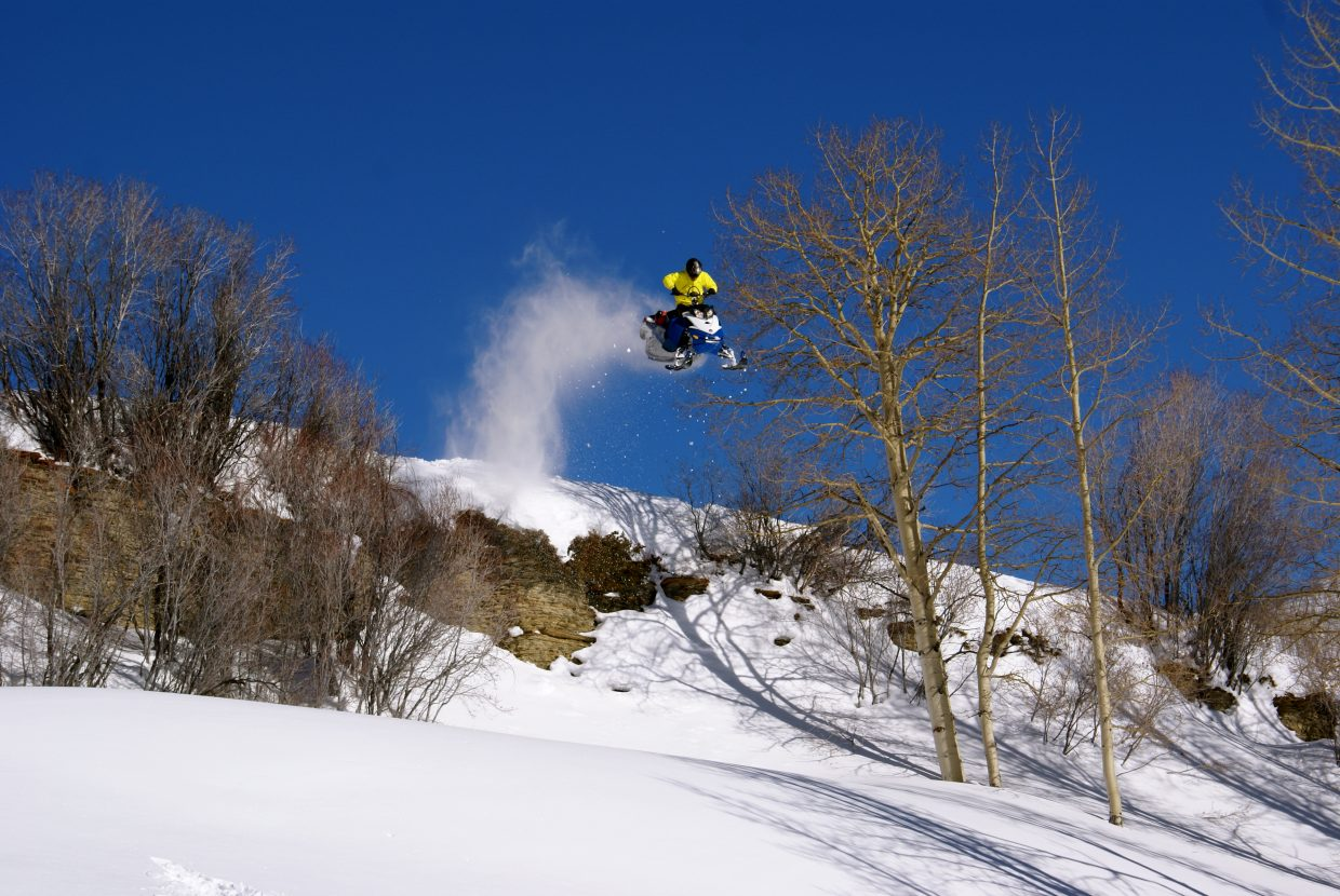 John Asta flies over a hill on his snowmobile on a sunny day last season.