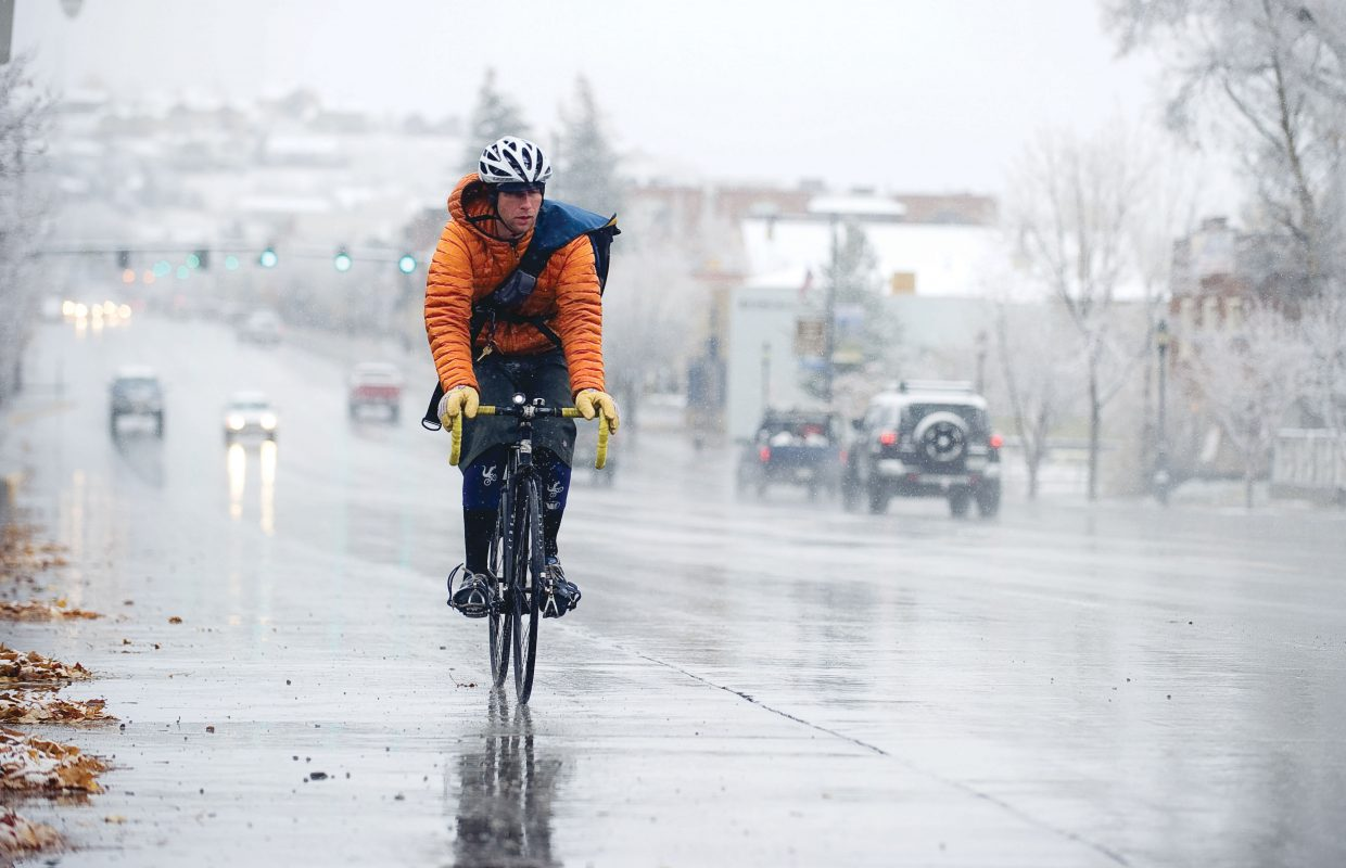Matthew Pronovost braves wet roads and falling snow as he rides his bike Wednesday to work at Moots.
