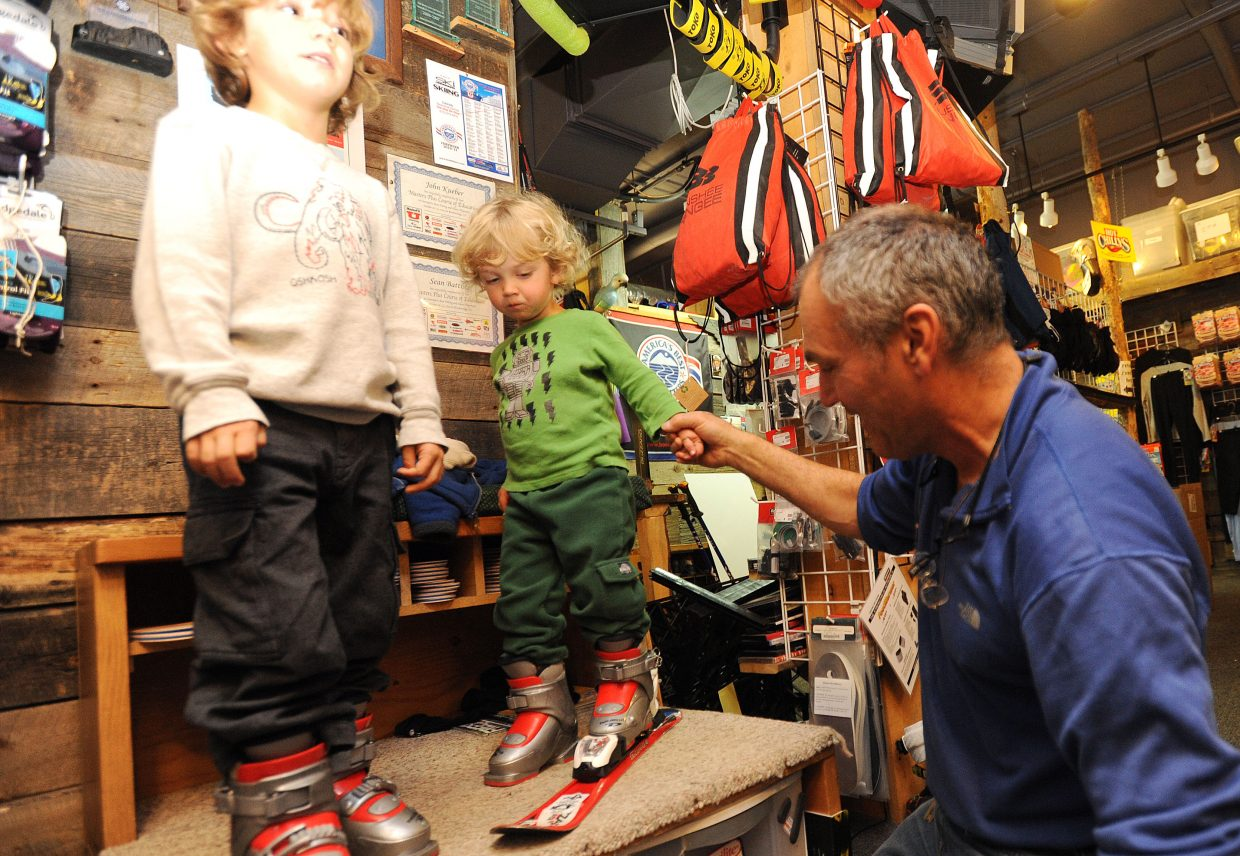 "One Stop Ski Shop owner John Kole helps Caden Sulentich, 2, into his first pair of rental skis Wednesday. Caden will be hitting the slopes this season for the first time. Big brother Jack Sulentich, 5, left, also was getting fitted for his season-long rental gear. He's no rookie, though, and said he's already been tearing up the snow ""for a long time."""