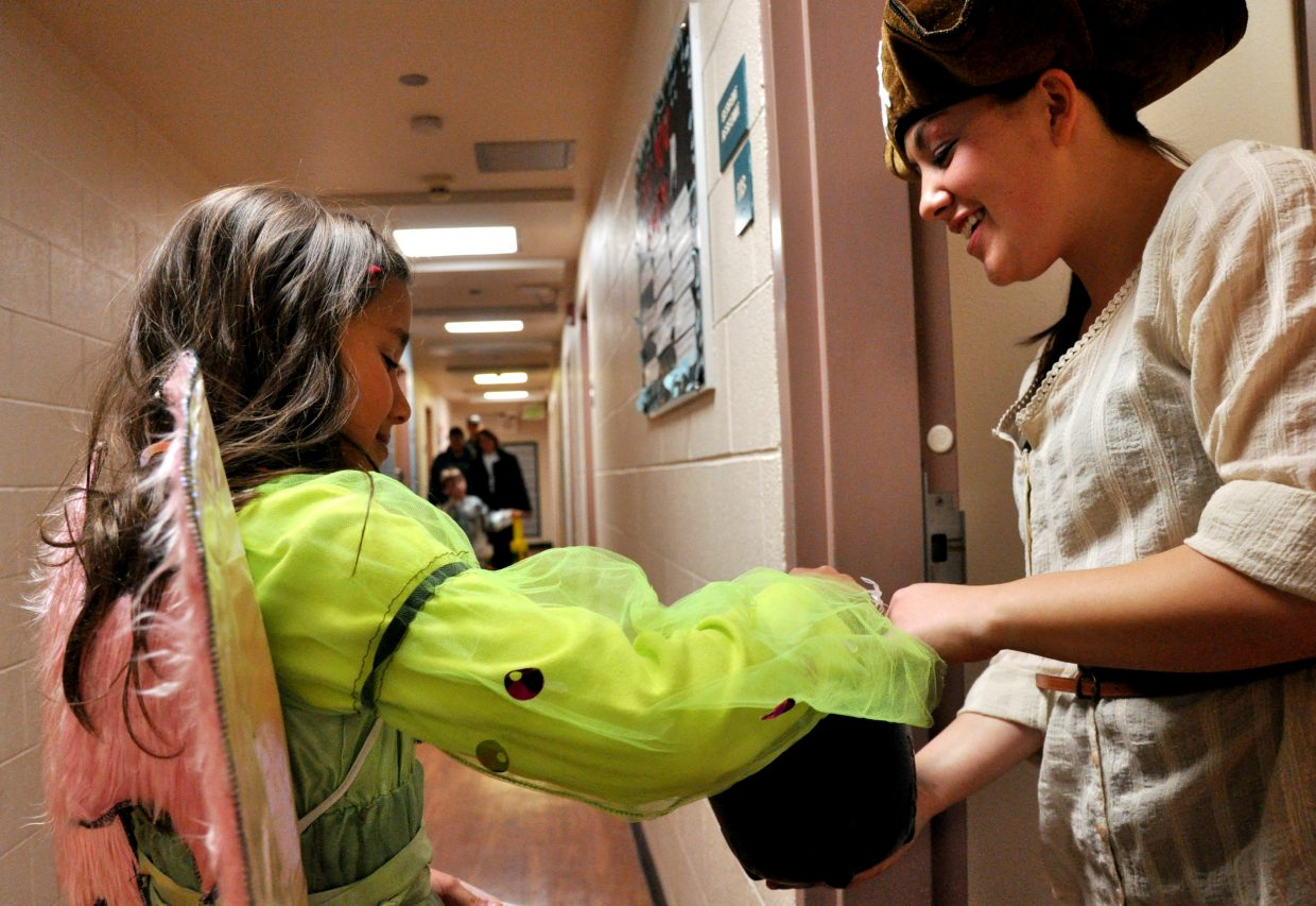 Julia Simoes, left, reaches in for a handful of candy being given out by Colorado Mountain College's Alpine Campus student Lizzy Marchiano at the college's Hill Hall. Julia was one of several children who went trick-or-treating Sunday night at the college dorm's Enchanted Castle event.
