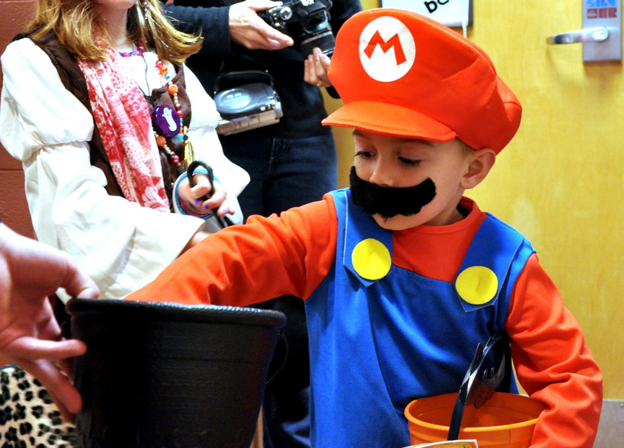 Ricky Hernandez, dressed as Mario, reaches in to grab some candy from Colorado Mountain College student Matt Morris during 2017's Enchanted Castle trick-or-treat event in Hill Hall.