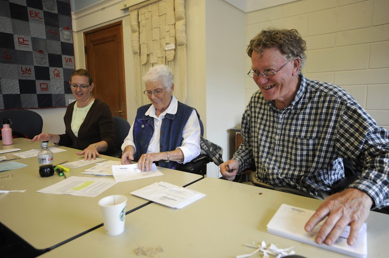 Election judges, from right, John Marshall, Ruth Ann Mewborn and Shauna Lamansky prepare ballots to be scanned Tuesday at the Routt County Courthouse.