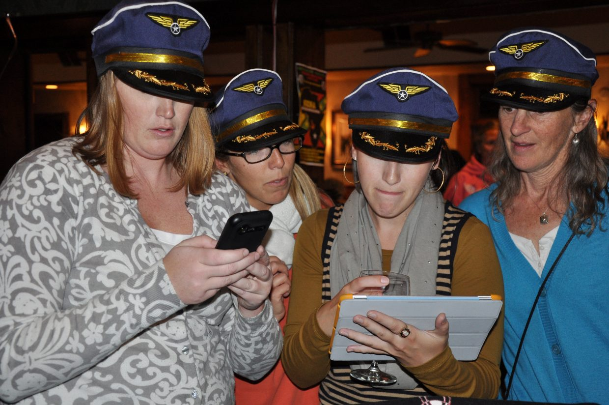 Resort Association employees from left Marion Tyler, Kara Stoller (then Givnish) and Morgan McDougald followed airline tax election returns on an iPad Tuesday with Ski Corp. Airline Program Director Janet Fischer in 2011. The tax was allowed to sunset in 2016, but resort officials are pursuing a new sales tax this year.