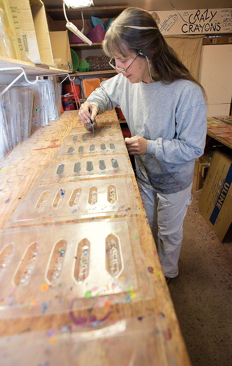 LuAnn Foty pours melted down crayons into molds in her Milner workshop.