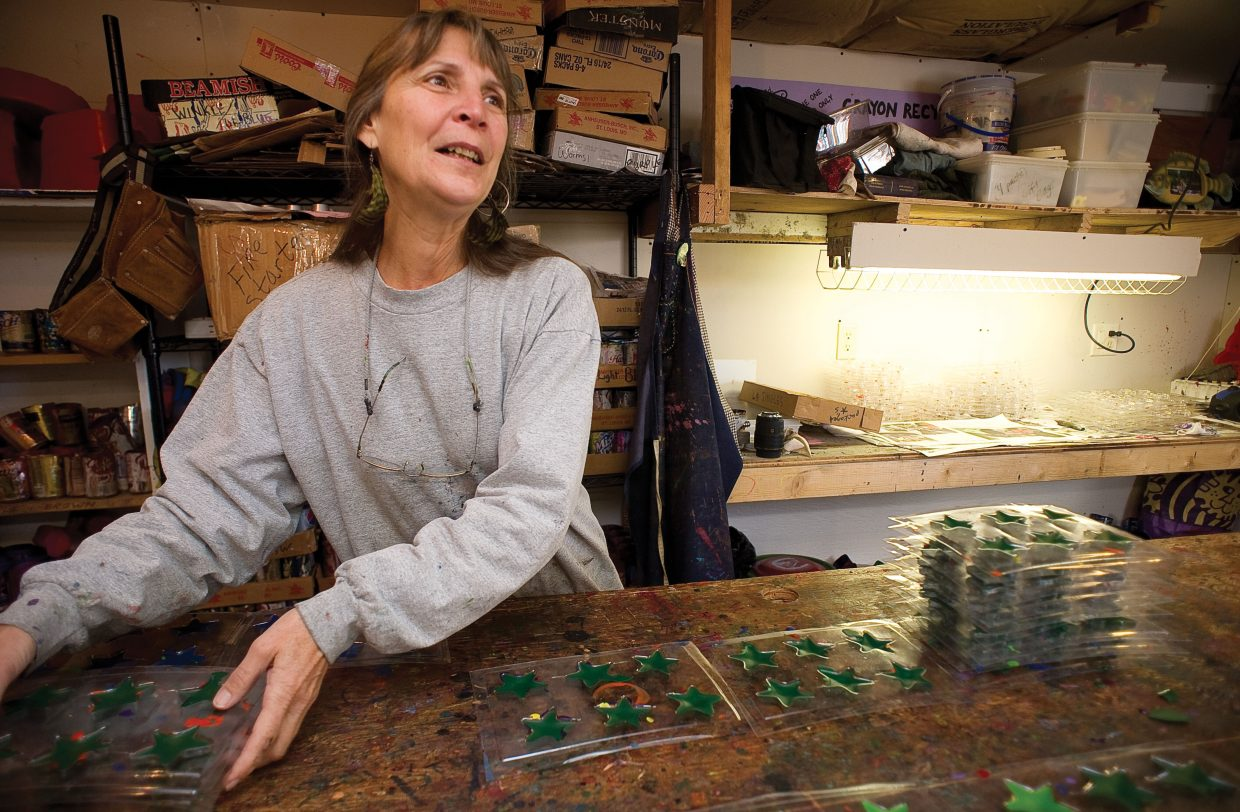 LuAnn Foty stacks molds filled with recycled crayons as she talks about why her business is important.