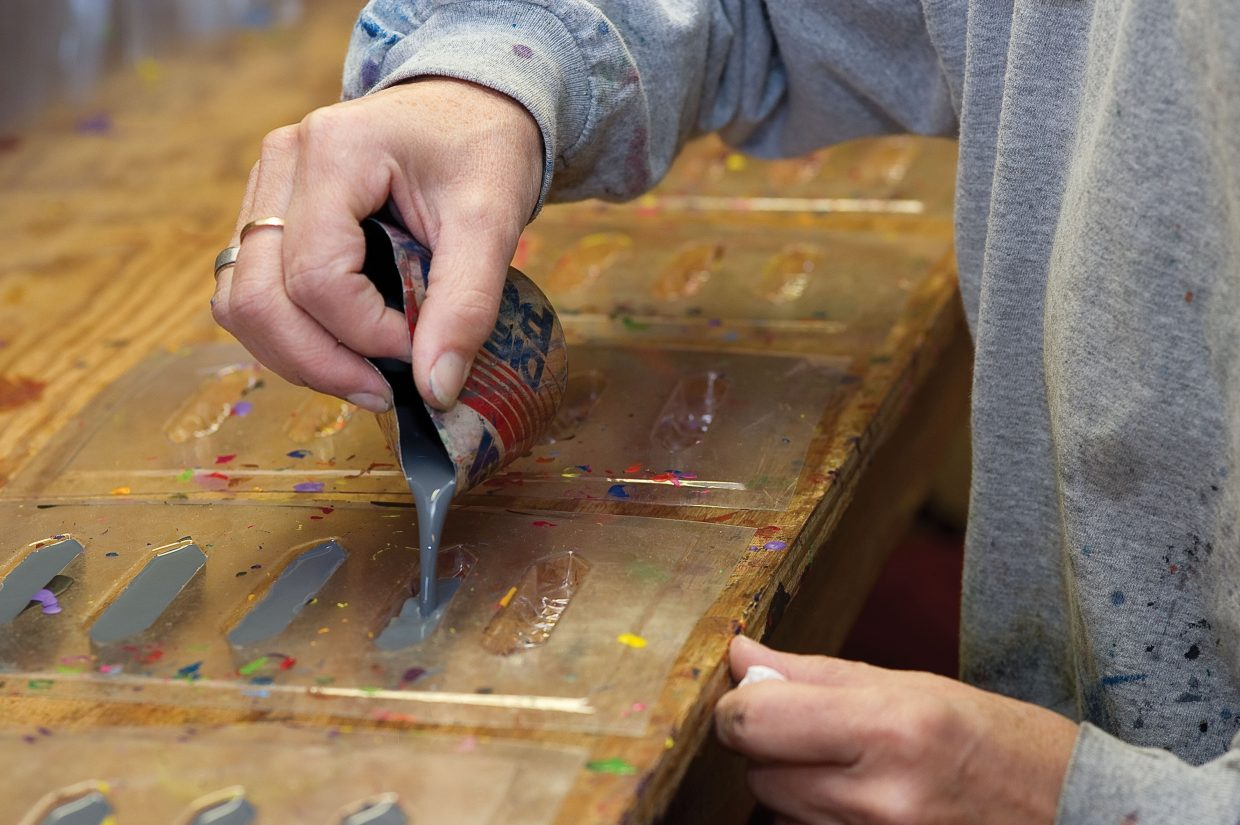 LuAnn Foty pours melted crayons into molds as part of the recycling process.