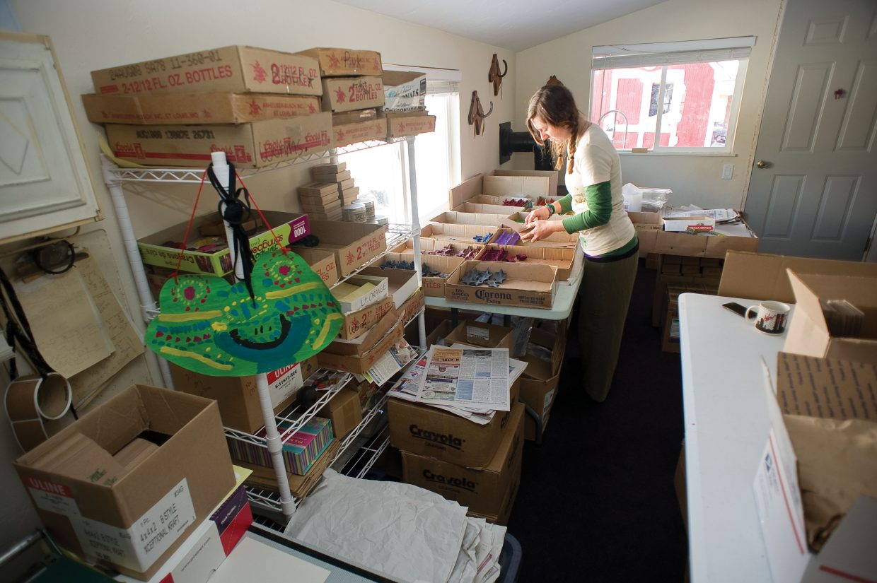 A helper packs boxes of recycled crayons for shipment inside the home and workshop of LuAnn Foty.