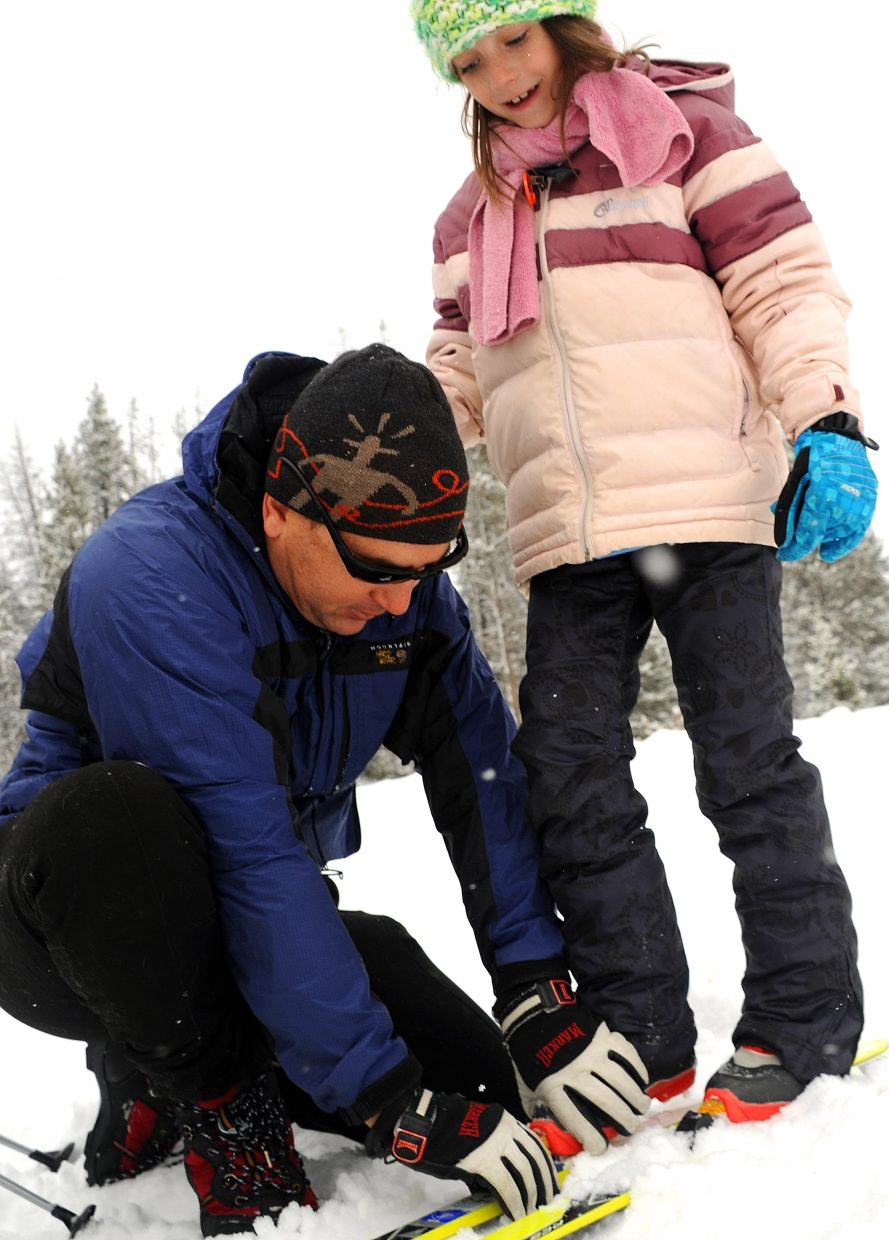 Josh Miller clips daughter Maggie Miller, 7, into her skis Sunday at Bruce's Trail on Rabbit Ears Pass.