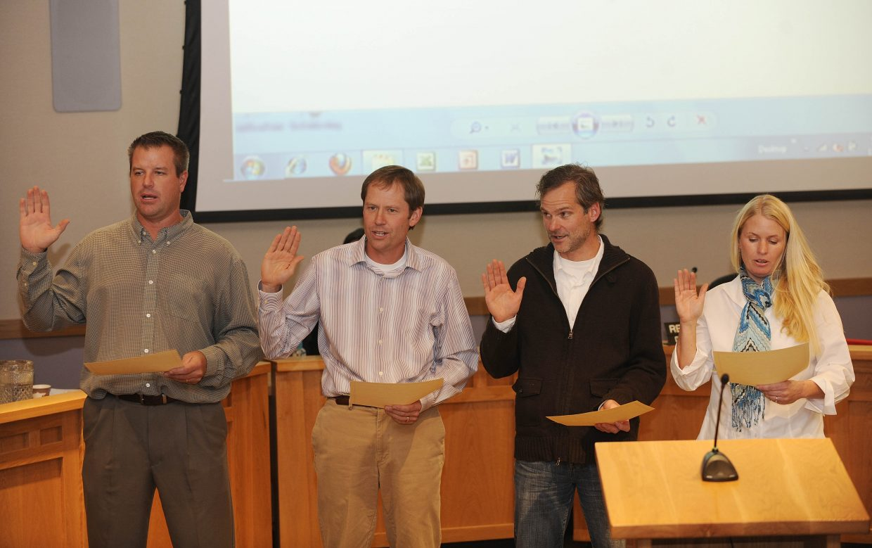 Steamboat Springs City Council members, from left, Kevin Kaminski, Bart Kounovsky, Scott Myller and Sonja Macys are sworn in during Tuesday night's meeting at Centennial Hall.