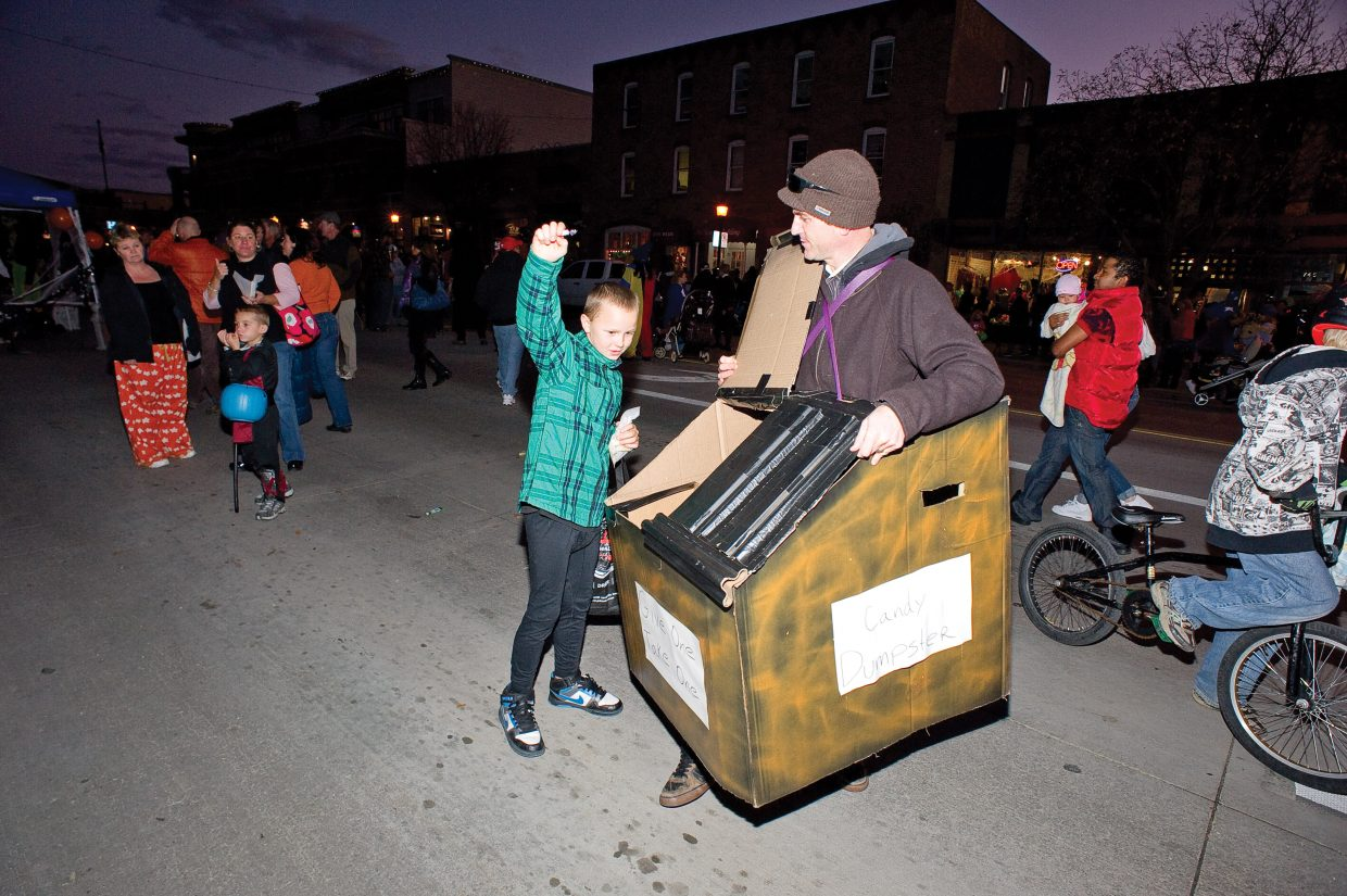 Willie Martin gets a piece of candy from Frank Cutler who dressed as the Candy Dumpster for this year's Downtown Halloween Stroll on Lincoln Avenue.