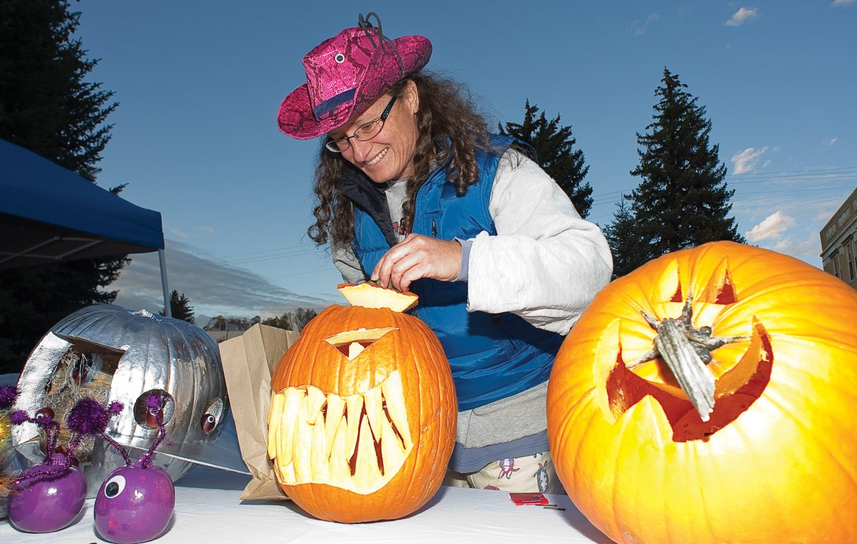 Janette Manke lights her husband's pumpkin during this year's Downtown Halloween Stroll on Lincoln Avenue.