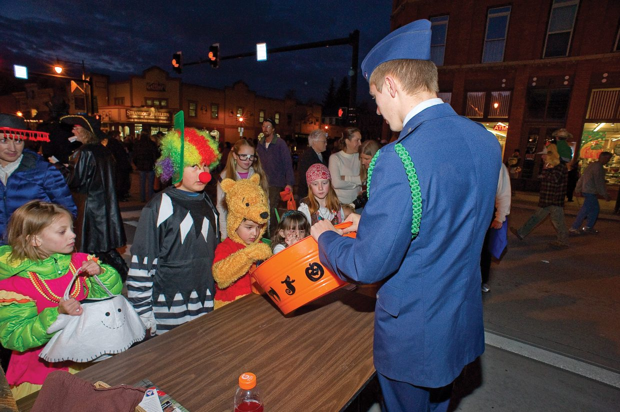 Garrett Pohlman hands out candy to children at a Civil Air Patrol booth located on Lincoln Avenue during this year's Downtown Halloween Stroll on Lincoln Avenue.