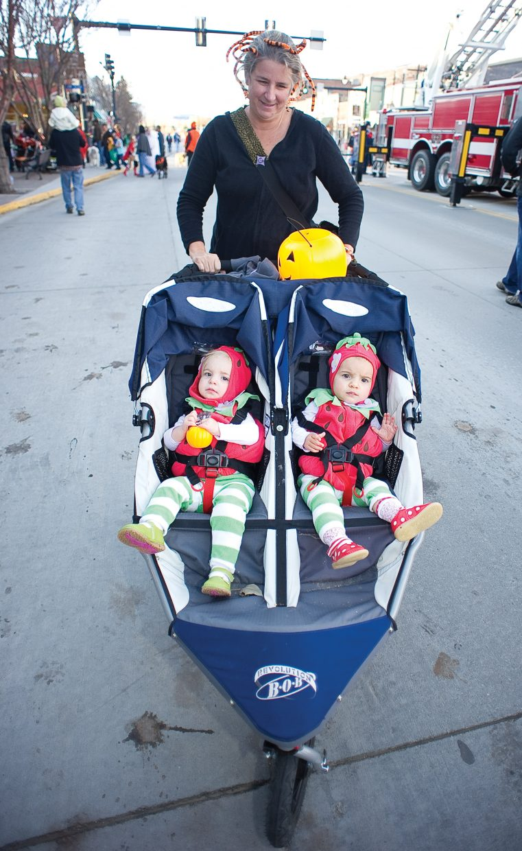 Beth Stevens pushes Nora, left, and Alice, rightt, Stevens along Lincoln Avenue at Monday's annual Downtown Halloween Stroll on Lincoln Avenue.