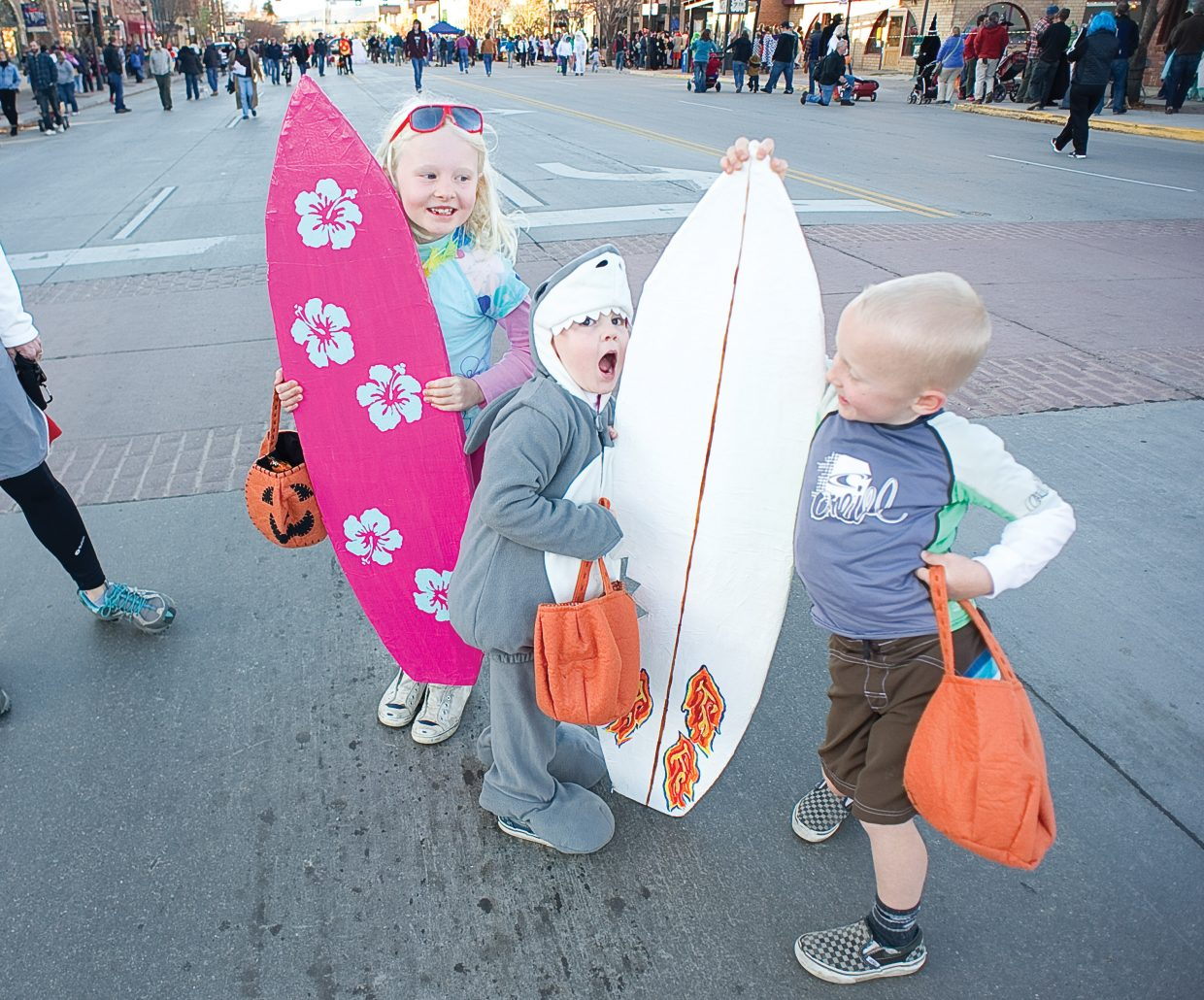 George Redfern looks to take a bite out of his brother Mac's surfboard as his sister Margaret watches the action unfold at Monday's annual Downtown Halloween Stroll on Lincoln Avenue.