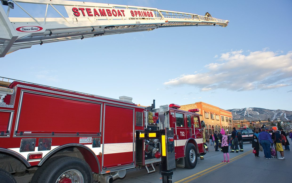 A member of the Steamboat Springs Fire Rescue makes his way up the ladder during Monday's annual Downtown Halloween Stroll on Lincoln Avenue.