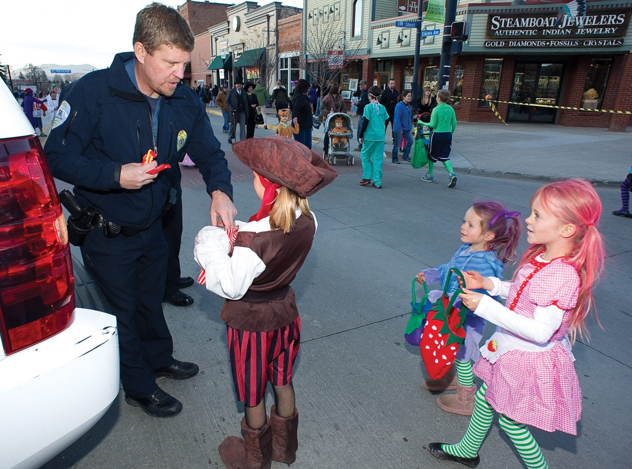 Steamboat Springs Police Capt. Joel Rae hands out candy during Monday's annual Downtown Halloween Stroll on Lincoln Avenue.