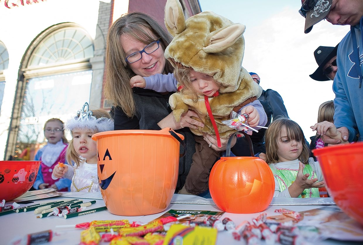 Two-year-old Lily Garey gets a helping hand from mom, Lindsey, as she grabs a handful of candy during the annual Downtown Halloween Stroll on Lincoln Avenue.