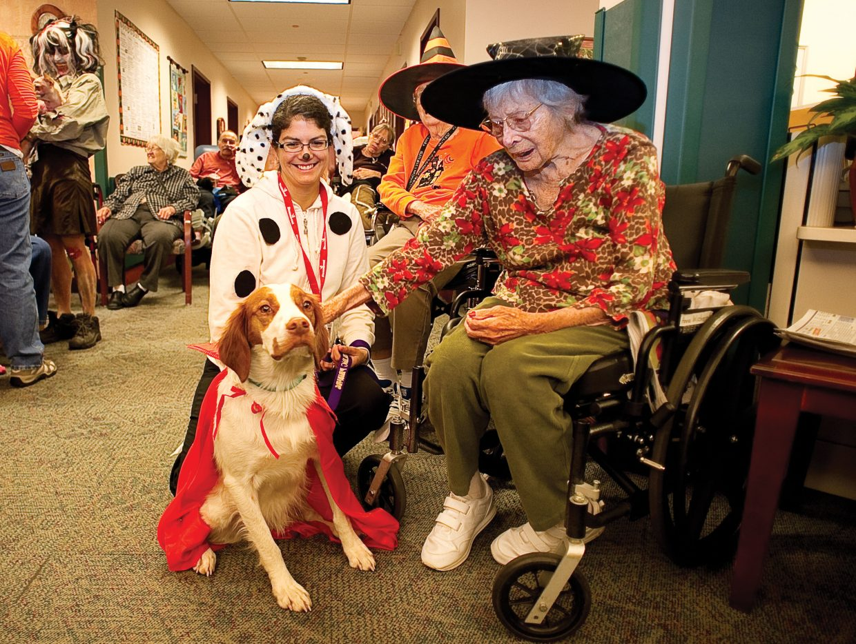 Doak Walker Care Center resident Anna Wichern visits with Remi and owner Lisa Warner on Monday afternoon. Members of the Heeling Friends group dressed up in costume to visit residents on Halloween.