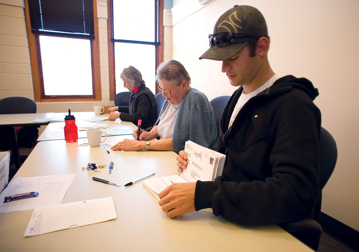 Election judges, shown front to back, Jace Bonner, Barb De Vries and Barbara Marshall process ballots Monday inside the Routt County Courthouse. The mail-in ballots have been pouring in for Tuesday's election and are being processed by judges inside the courthouse. No tallies will be taken until after the polls close at 7 p.m. Tuesday.