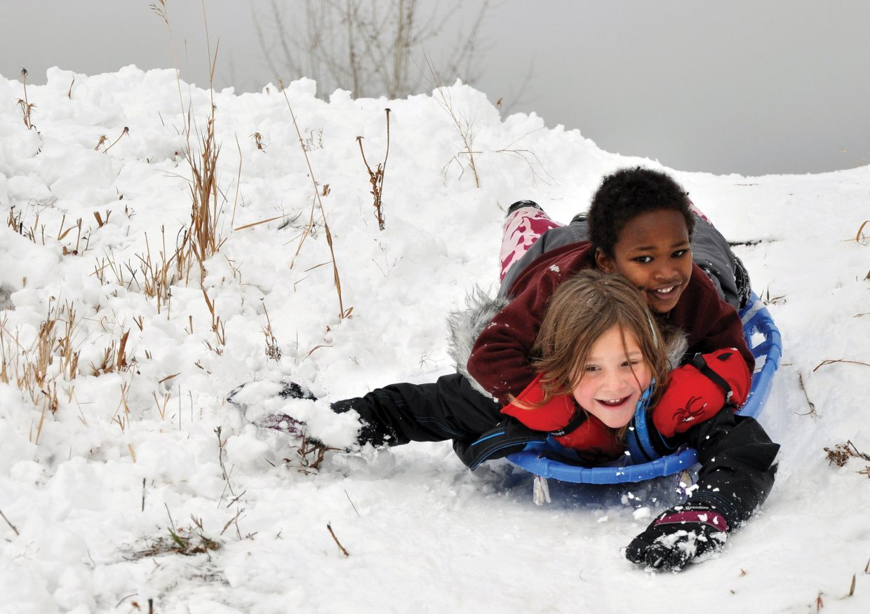 Josey Foote and her brother Aklilu Foote sled down a hill Sunday near Park Avenue in Steamboat Springs. Although some enjoyed the snow that a weekend storm brought to town, the snow and ice caused a number of accidents in the area.