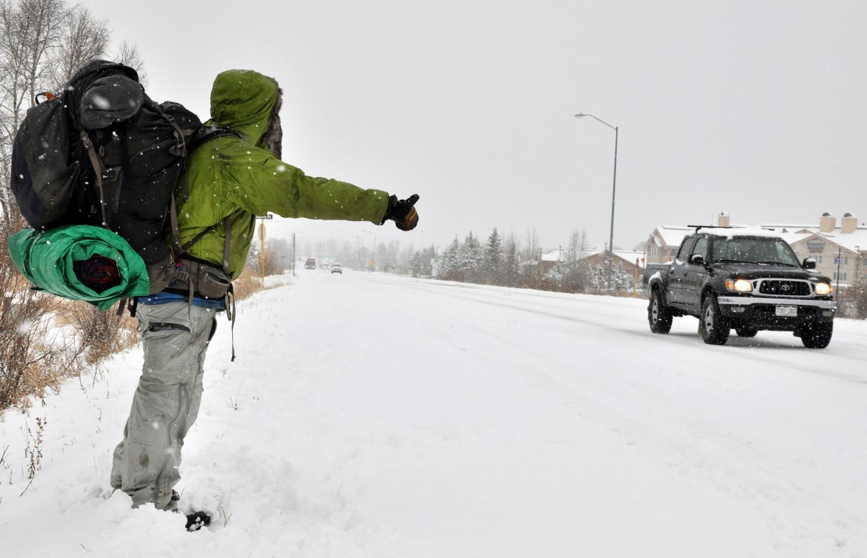 Ray Burns attempts to flag down a ride to Denver on Sunday along U.S. Highway 40 in Steamboat Springs.
