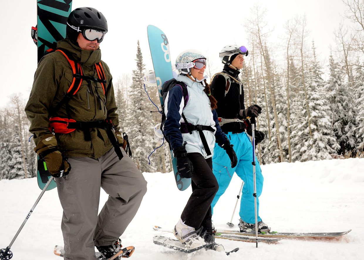 Scott Nixon, from left, Lindsay Nixon and Matt Gorevan hike into the backcountry Sunday. The weekend's winter storm blanketed the high country with snow, giving eager locals a preview of what the season has in store.