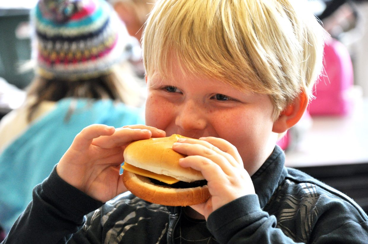 """Soda Creek Elementary School student Baden Park takes a bite of a Sweetwood Cattle Co. burger Monday. The Steamboat Springs beef producer donated 1,400 beef patties to the Steamboat Springs School District, and the burgers will be served to students through Thursday. """"It's a nice treat for the kids because I know they miss the hamburgers,"""" Steamboat Nutritional Services Director Max Huppert said. He said burgers haven't been on the district's lunch menu for about two years."""