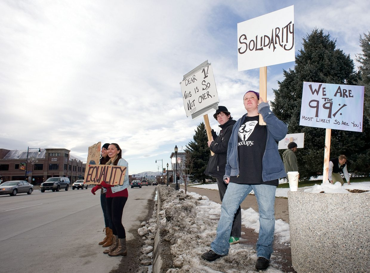 Protester Sarah Whitecrane holds a sign as motorists pass by during an Occupy Steamboat demonstration Thursday afternoon in front of the Routt County Courthouse. Herrera was part of a group that showed up to participate in the Occupy movement's day of action. Local demonstrators came out to protest the greed of the nation's wealthiest 1 percent and show their support for the Occupy movement, which has spread across the country.