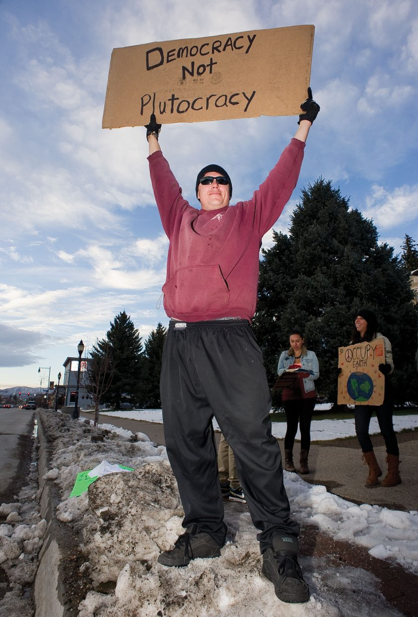 Isaac Solbodnik holds a sign during an Occupy Steamboat protest Thursday in front of the Routt County Courthouse. Local demonstrators came out to recognize the national day of action and show support for the 2-month-old, nationwide Occupy movement.