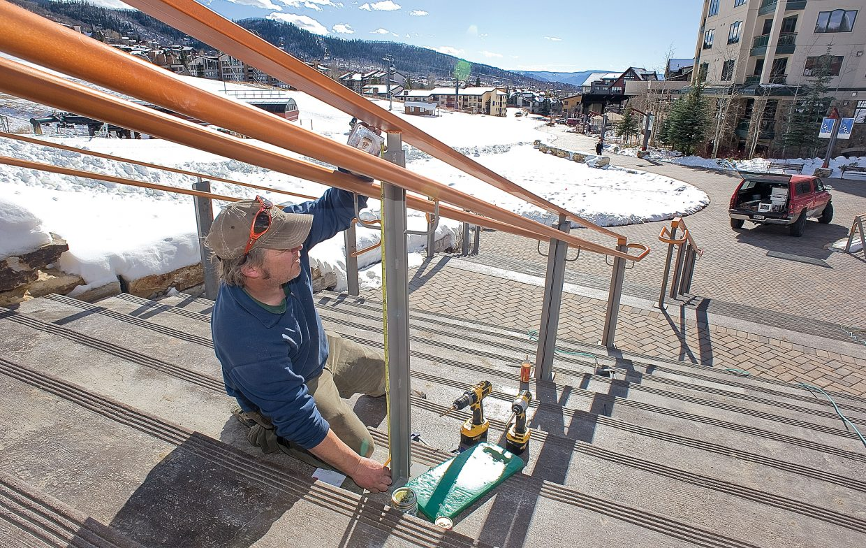 Tim Shorland, who is a subcontractor for Duckels Construction, works on a few last-minute details to get the new promenade at the base of Steamboat Ski Area ready for this week's Opening Day.