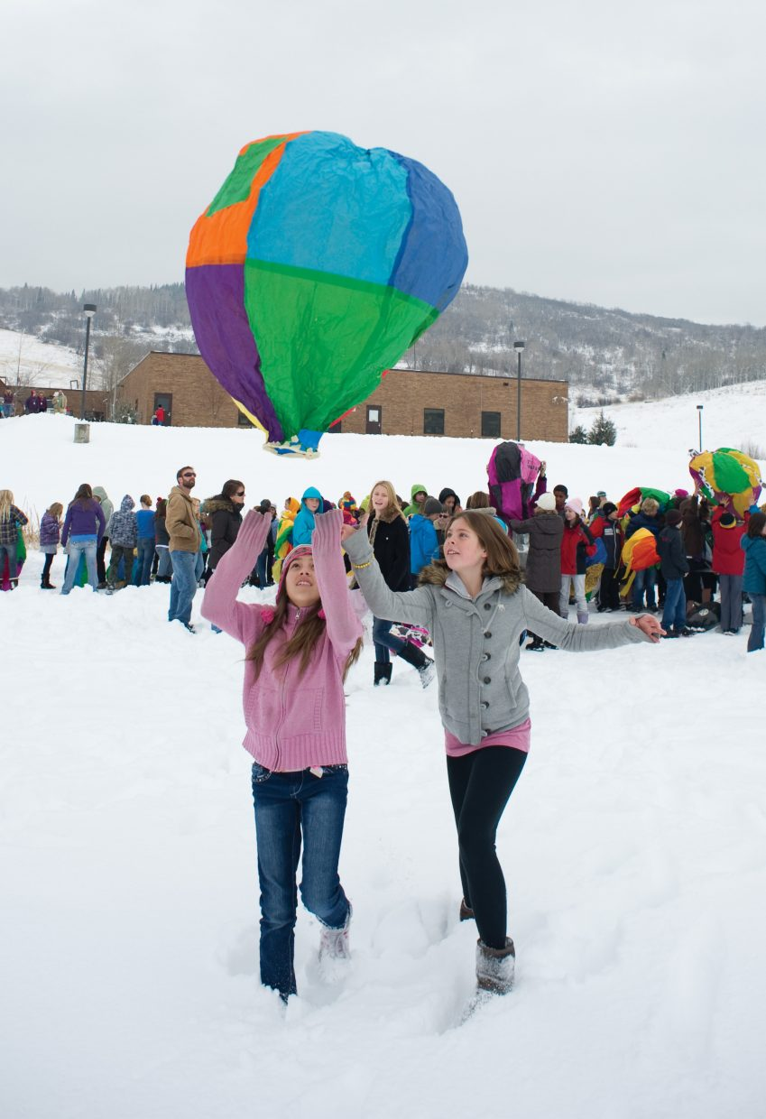 Sixth-graders Kailee Davis, left, and Aubrey Moothart chase the balloon they created in science class as it comes to a soft landing at the Steamboat Springs Middle School football field Monday morning.