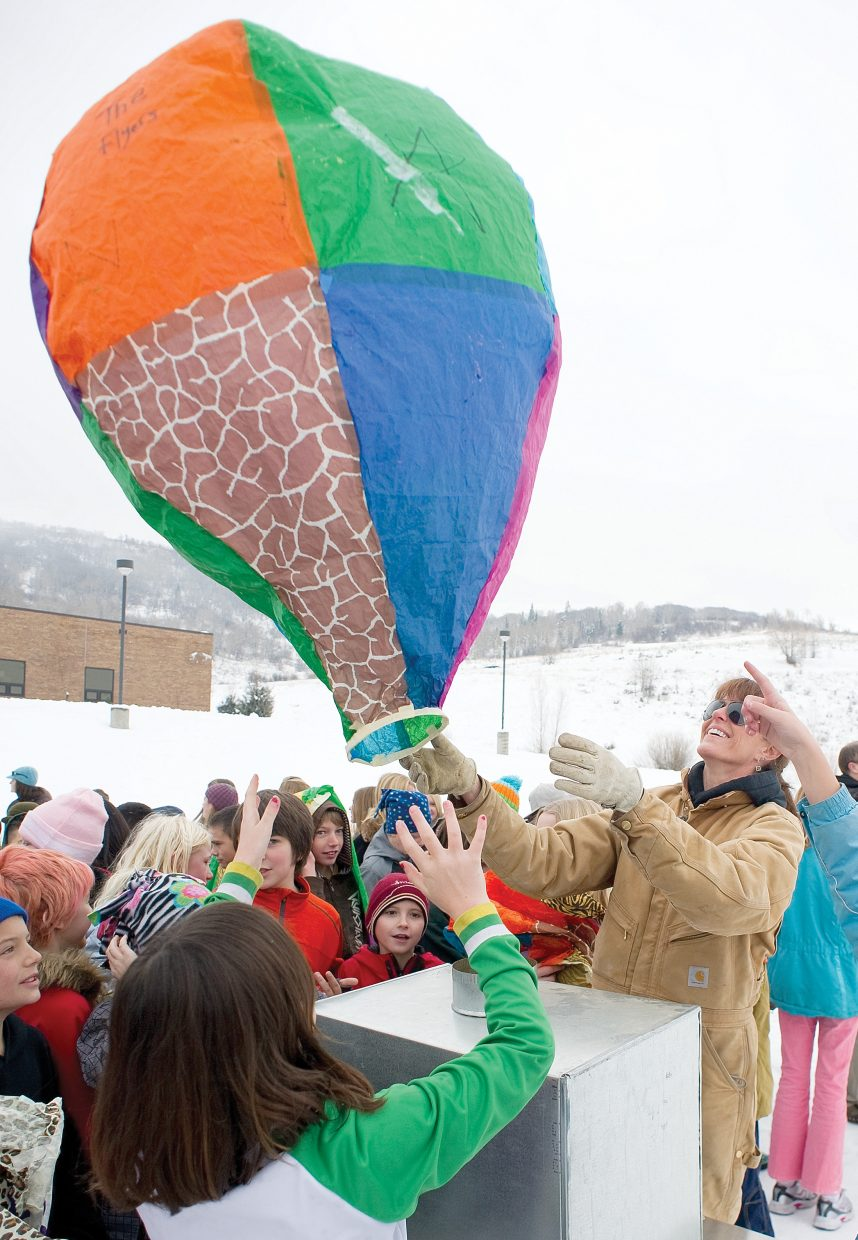 Sixth grade science teacher Tracy Bye helps students launch a hot air balloon at the Steamboat Springs Middle School football field.
